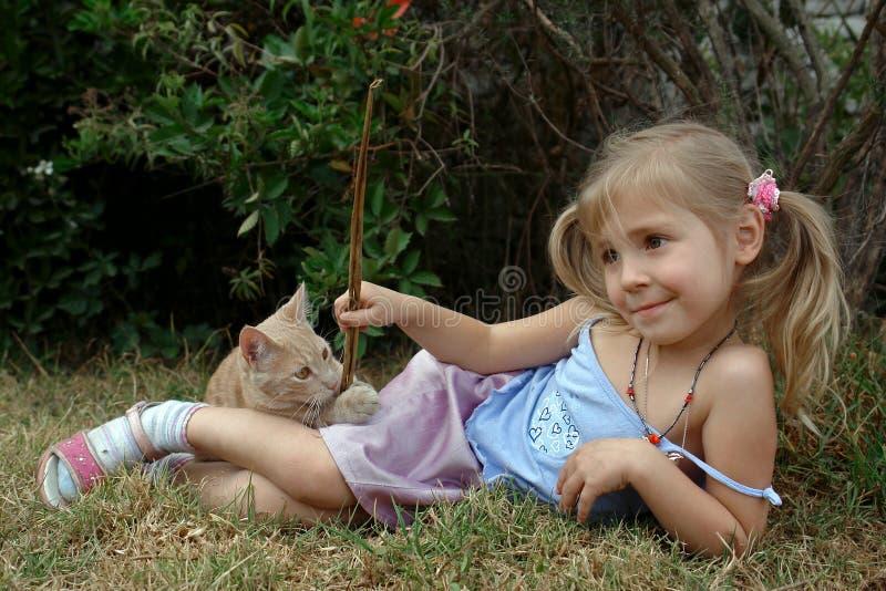 Juego de niños con el gatito fotografía de archivo