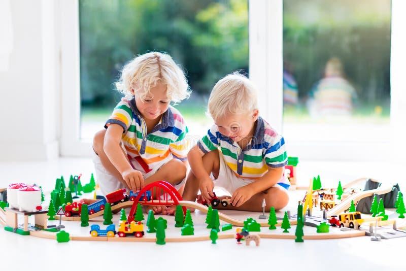 Juego de niños con el tren del juguete Embroma el ferrocarril de madera fotografía de archivo libre de regalías