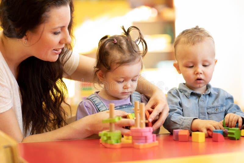 Juego de niños con formas y rompecabezas de madera colorido en una sala de clase del montessori foto de archivo