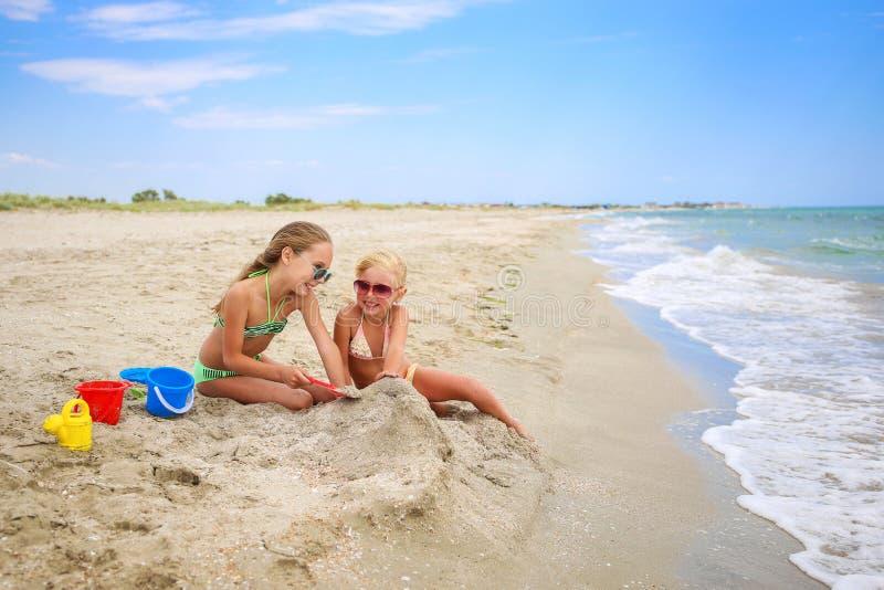 Juego de niños con la arena en la playa imagenes de archivo