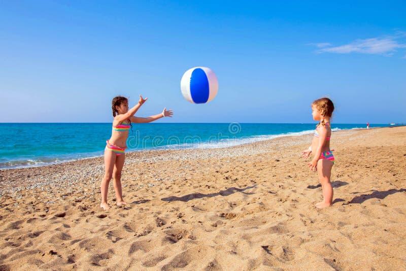 Juego de niños con la bola en la playa imágenes de archivo libres de regalías