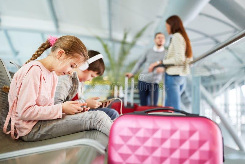 Juego de niños con la tableta y smartphone antes del vuelo imagen de archivo libre de regalías
