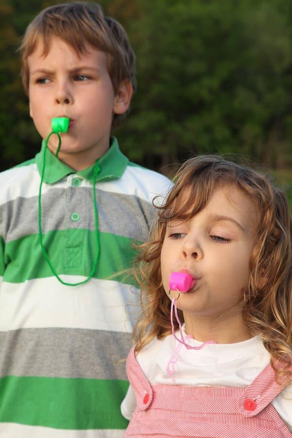 Juego de niños con los silbidos. foto de archivo