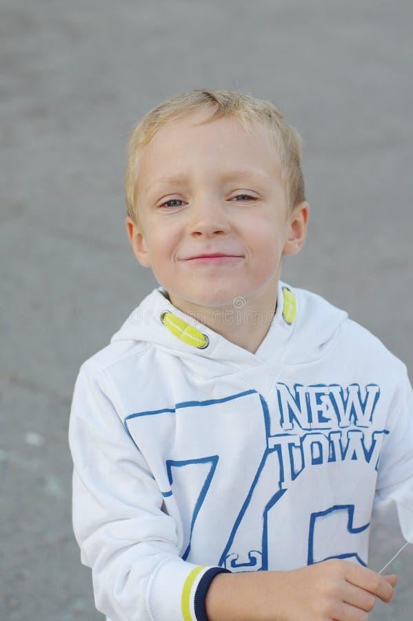 Juego de niños divertido y feliz en una cometa Se visten en las camisetas y los pantalones blancos Funcionamiento en la puesta de fotos de archivo libres de regalías