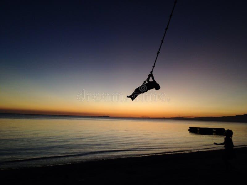 Juego de niños en la playa Filipinas de Siquijor de la puesta del sol del oscilación imagen de archivo libre de regalías