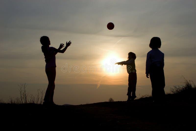 Juego de niños en puesta del sol imagen de archivo libre de regalías