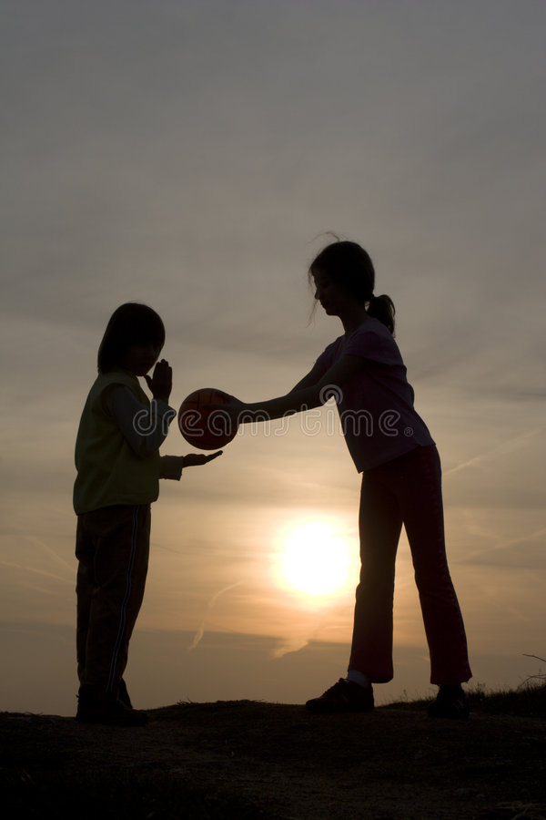 Juego de niños en puesta del sol imagenes de archivo
