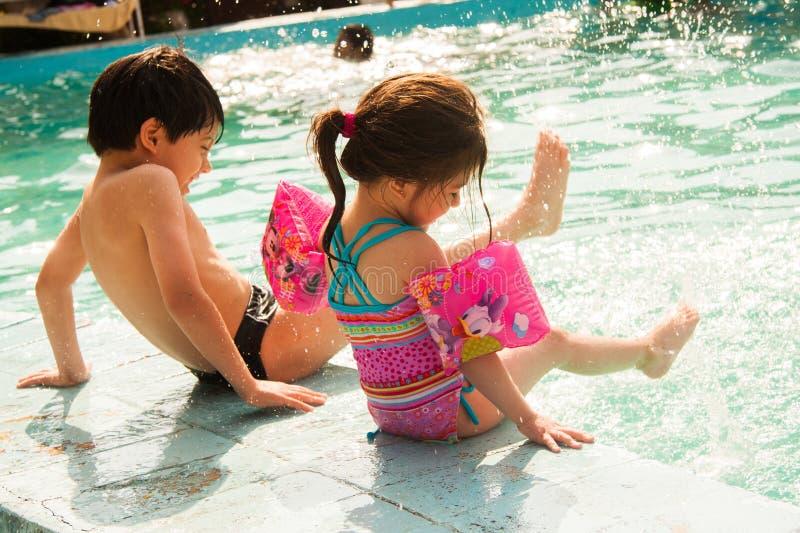 Juego de niños en una piscina en verano imagen de archivo