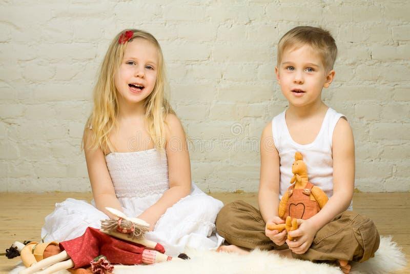 Juego de niños rubio sonriente con los juguetes fotografía de archivo