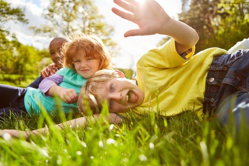 Juego de niños y tonto alrededor en un prado fotos de archivo