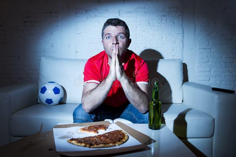 Juego de observación del hombre del fanático del fútbol en la TV en el jersey de equipo nervioso y la tensión foto de archivo libre de regalías