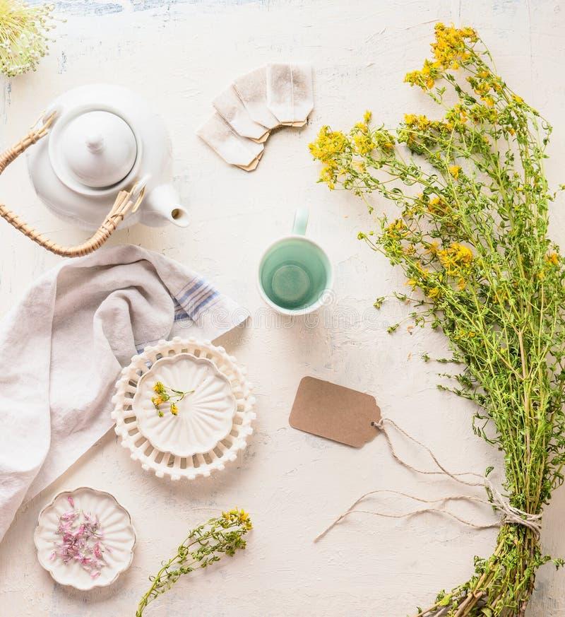 Juego de té blanco en la tabla ligera con el manojo de las hierbas y de las flores de cura, visión superior Infusión de hierbas c imagen de archivo
