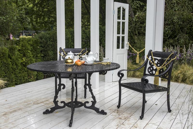 Juego de té en la tabla en el jardín Dise?o del paisaje imágenes de archivo libres de regalías