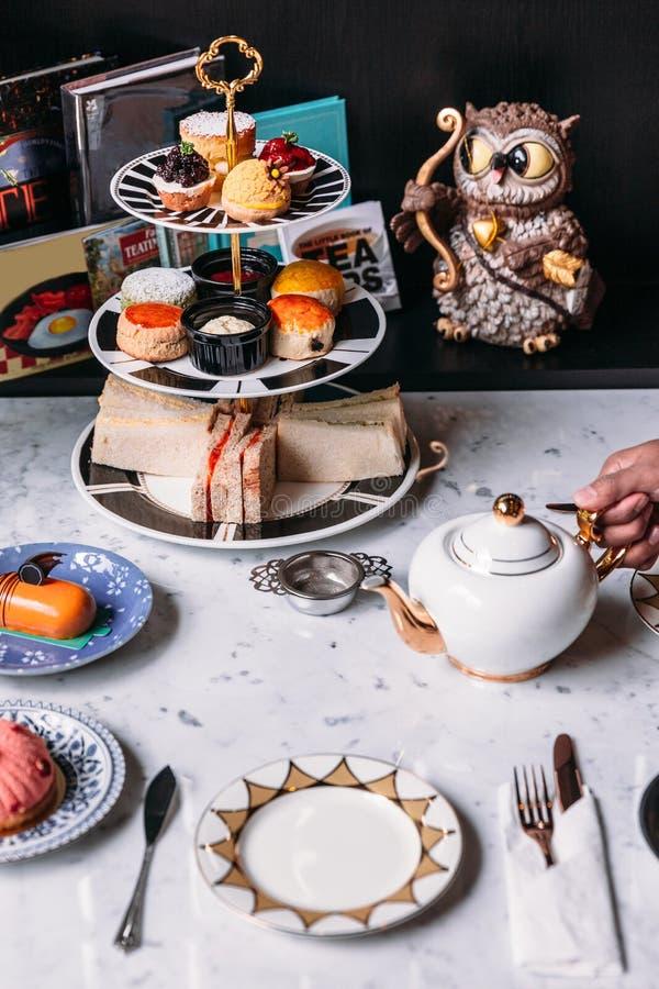Juego de té inglés de la tarde incluyendo té caliente, pasteles, scones, bocadillos y mini empanadas en la tabla superior de márm fotos de archivo libres de regalías