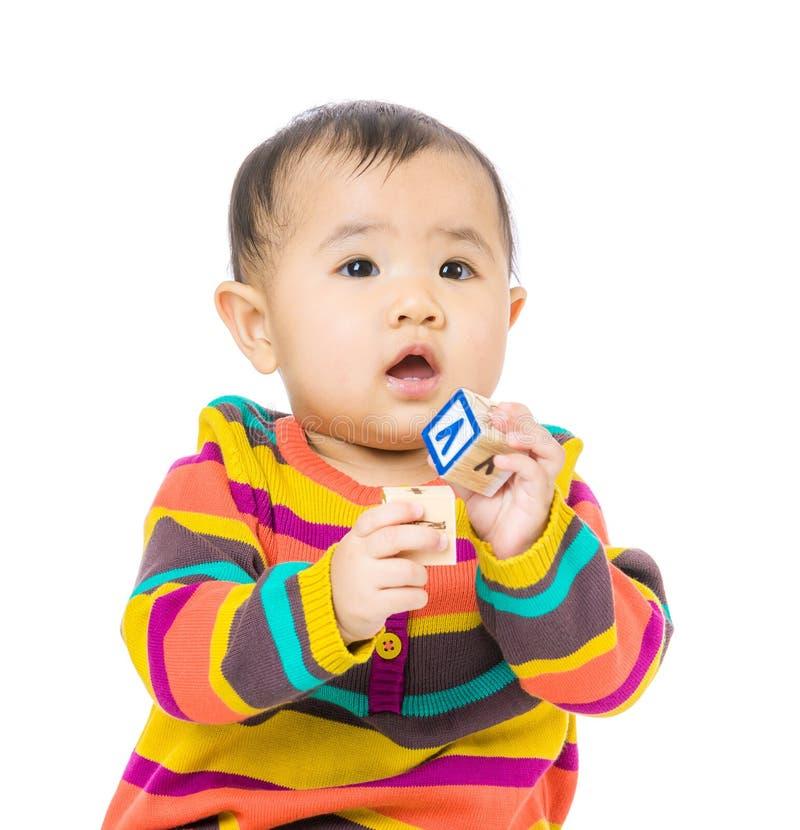 Juego del bebé de Asia con el bloque de madera del juguete imagen de archivo