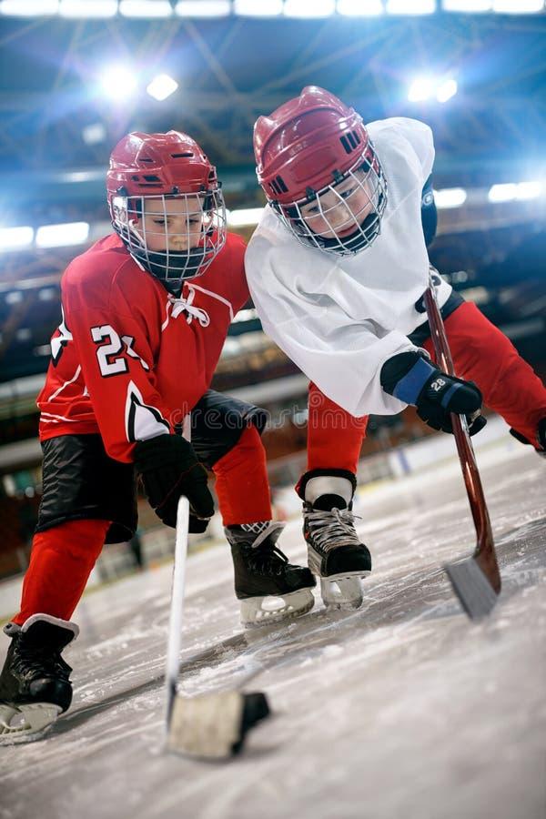 Juego del hockey sobre hielo - acción que golpea con el pie en meta foto de archivo