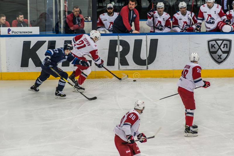 Juego del hockey sobre hielo, jugadores en la acci?n cerca del banco fotografía de archivo