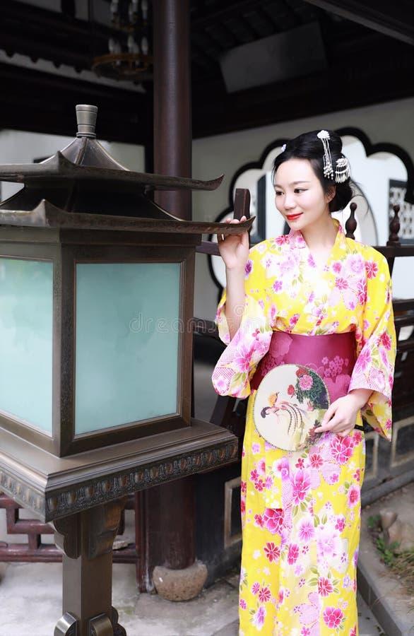 Juego del kimono de la mujer que lleva del geisha japonés asiático tradicional de la novia en un control del graden una fan imagen de archivo libre de regalías