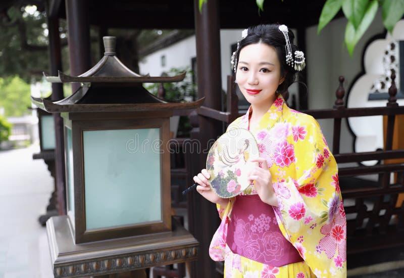 Juego del kimono de la mujer que lleva del geisha japonés asiático tradicional de la novia en un control del graden una fan fotografía de archivo libre de regalías