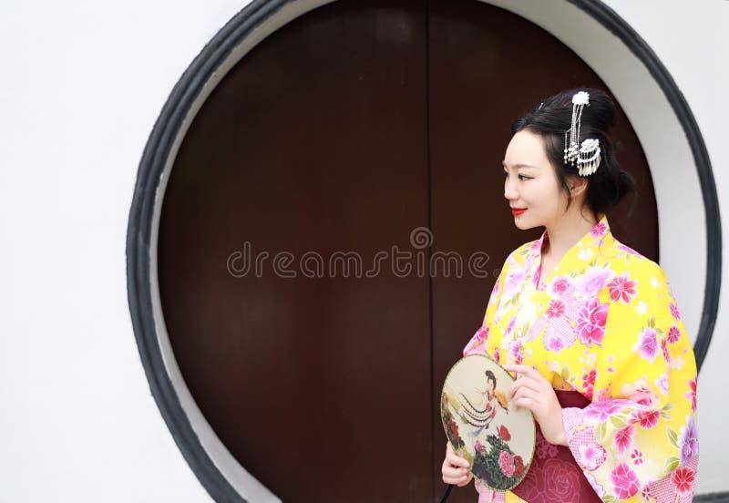 Juego del kimono de la mujer que lleva del geisha japonés asiático tradicional de la novia en un control del graden una fan fotografía de archivo