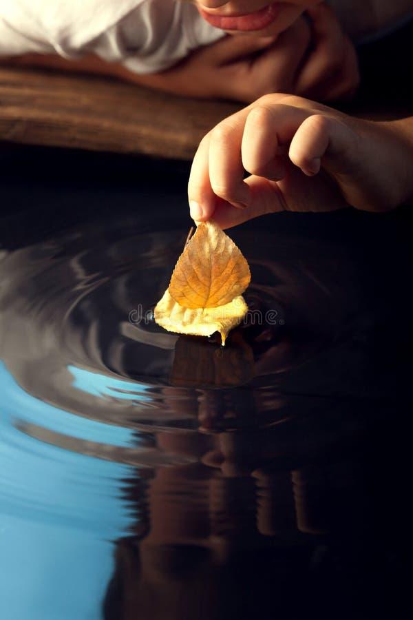 Juego del muchacho con la nave de la hoja en agua foto de archivo libre de regalías