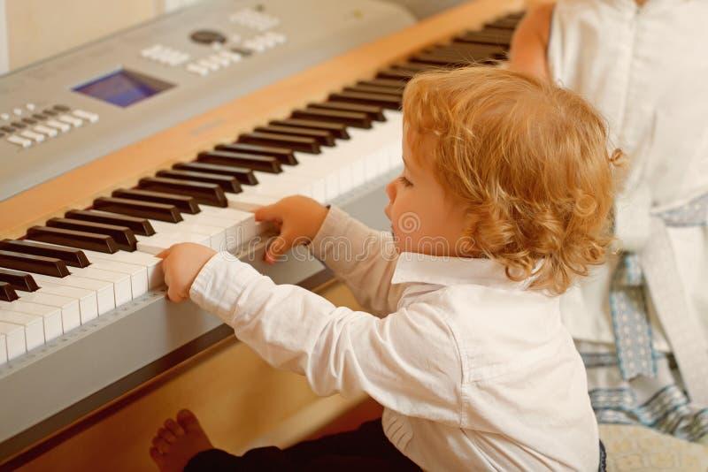 Juego del muchacho en piano digital fotos de archivo libres de regalías