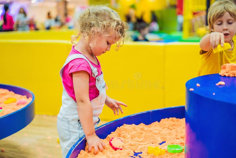 Juego del muchacho y de la muchacha con la arena cinética fotografía de archivo libre de regalías