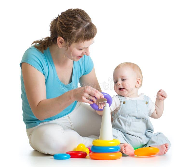 Juego del niño y de la mamá con los juguetes del bloque fotografía de archivo
