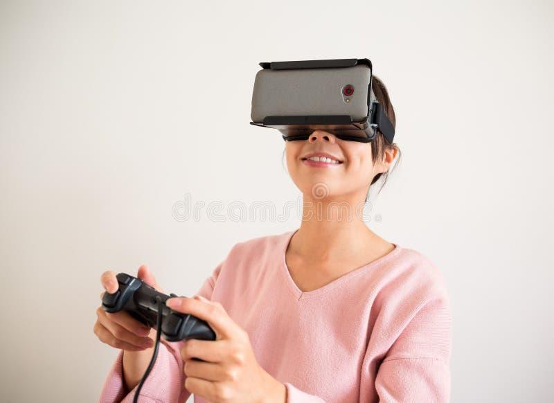 Juego emocionado del juego de la mujer con el dispositivo de la realidad virtual imagen de archivo libre de regalías