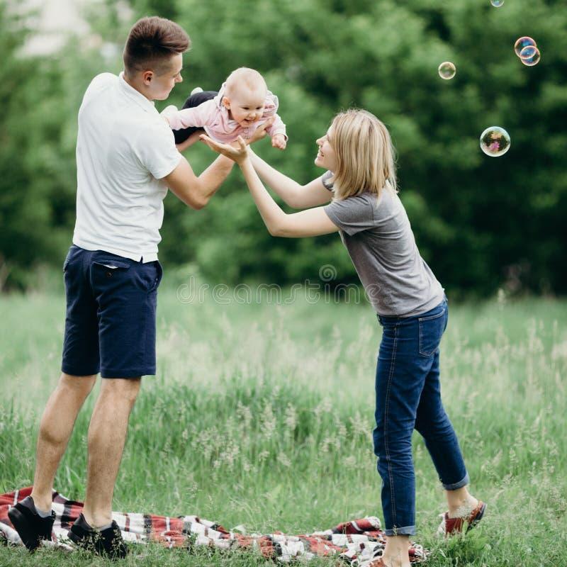 Juego feliz de la familia al aire libre, soplando burbujas de jabón fotografía de archivo