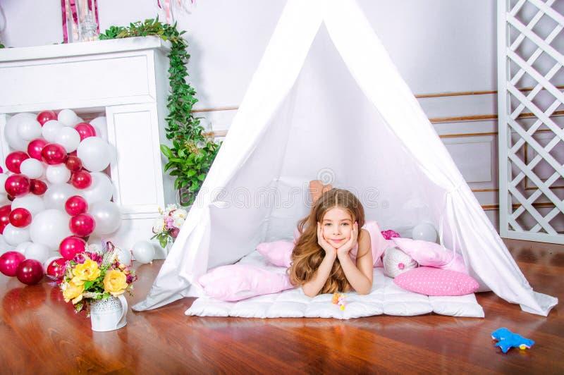 Juego feliz de la muchacha en casa Niño divertido que se divierte en sitio de niños fotos de archivo