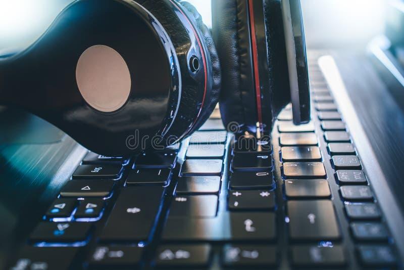 Juego inalámbrico negro o Deejay Headphone Lying On un teclado de ordenador con la luz brillante en el fondo fotografía de archivo