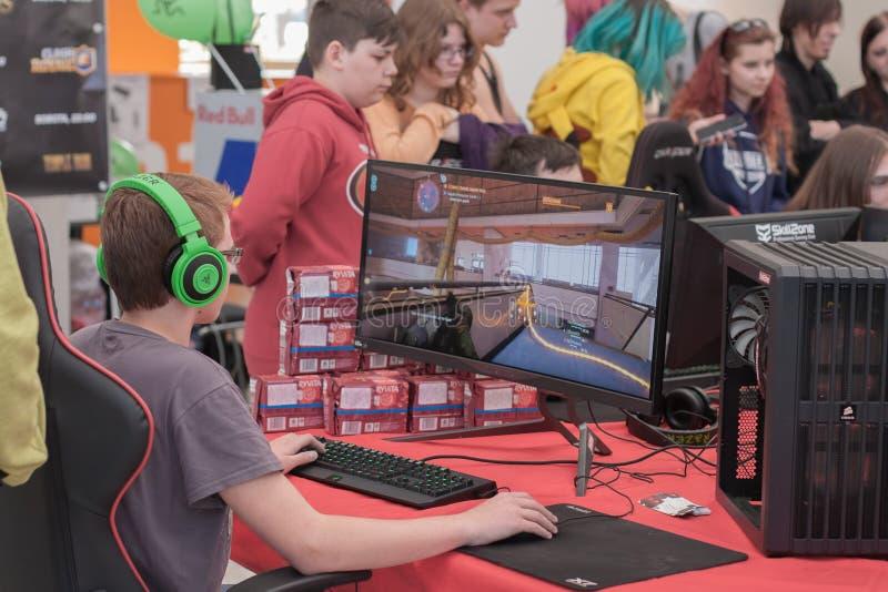 Juego joven del juego del muchacho en de computadora personal en Animefest fotografía de archivo