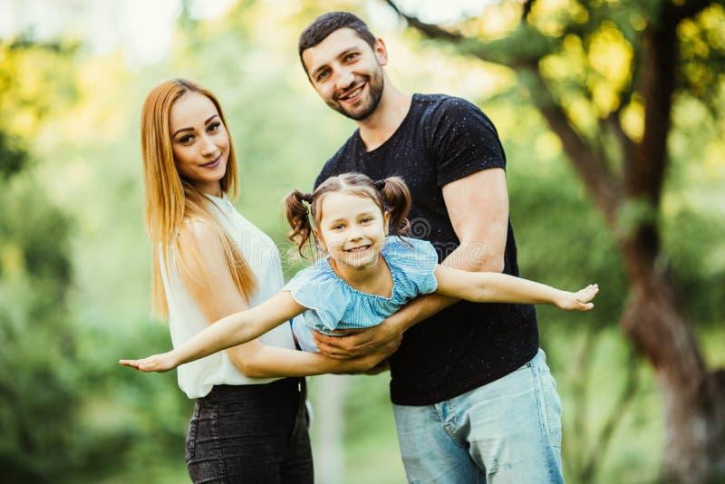 Juego joven feliz de la familia en parque del verano La madre, el padre y la hija vuelan en el parque del verano imágenes de archivo libres de regalías
