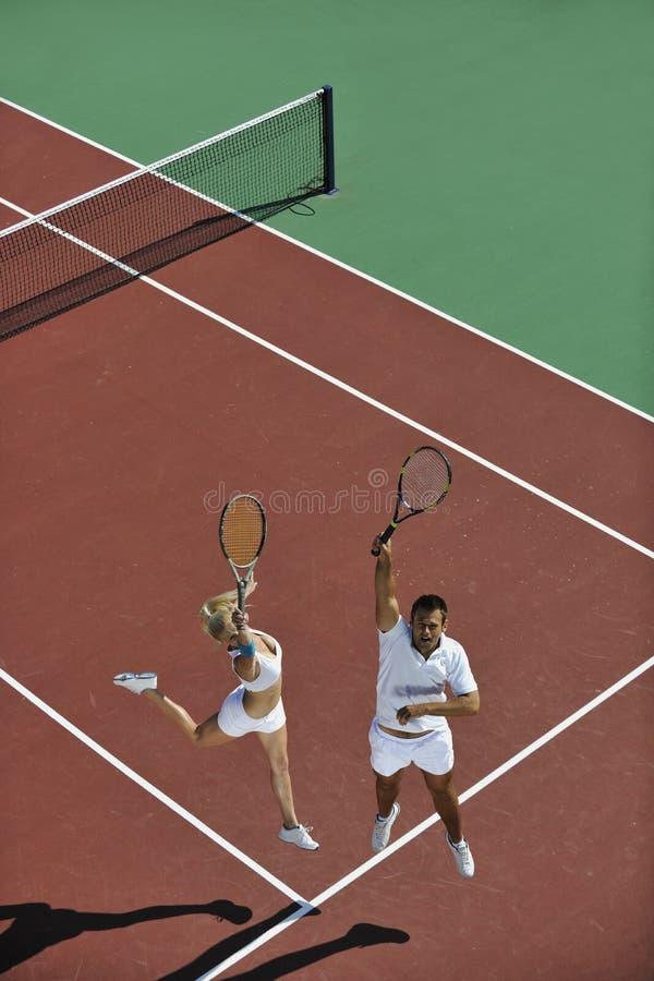 Juego joven feliz del tenis del juego de los pares al aire libre imagenes de archivo