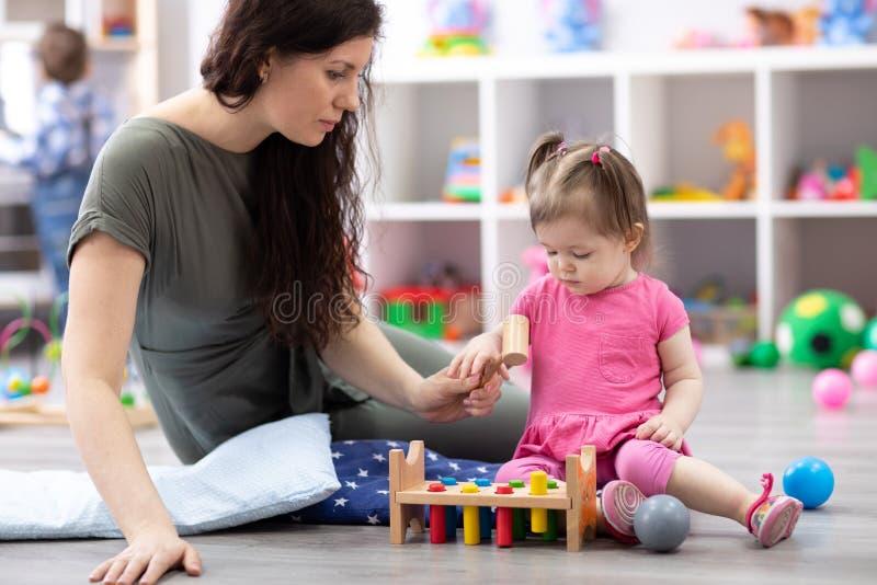Juego lindo del bebé con cuidador o la niñera en cuarto de niños o guardería foto de archivo libre de regalías