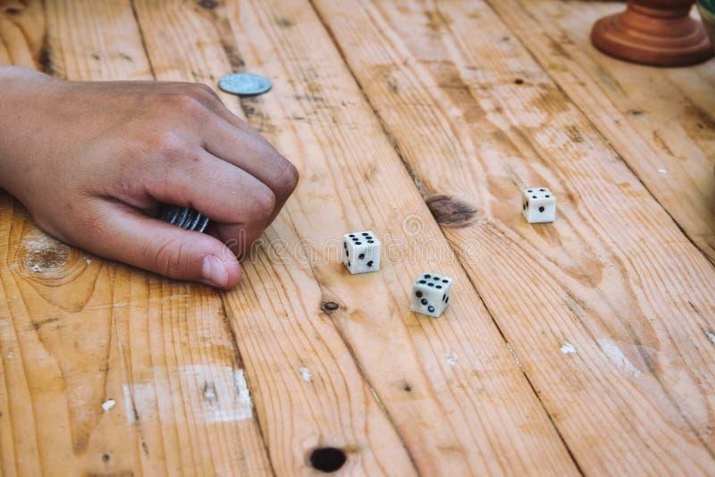 Juego mientras que juega a un juego con los dados en una tabla de madera fotos de archivo