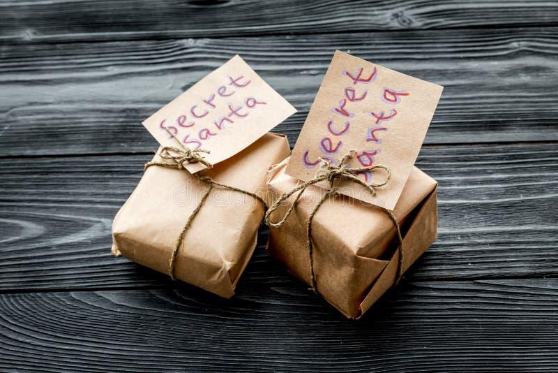 Juego tradicional de la Navidad Cajas de regalo envueltas con las notas manuscritas Papá Noel secreto en cierre de madera oscuro  imagen de archivo libre de regalías