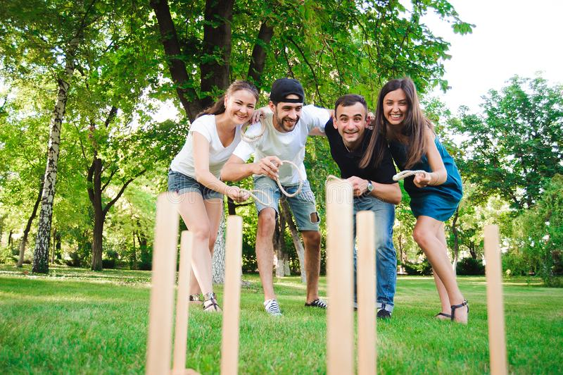 Juegos al aire libre - lanzamiento del anillo, amigos que juegan lanzamiento del anillo en un parque imágenes de archivo libres de regalías