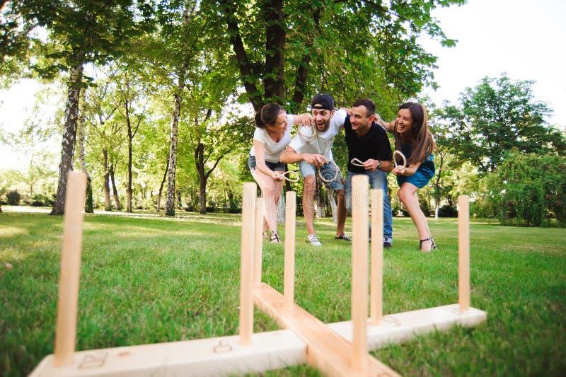 Juegos al aire libre - lanzamiento del anillo, amigos que juegan lanzamiento del anillo en un parque fotos de archivo
