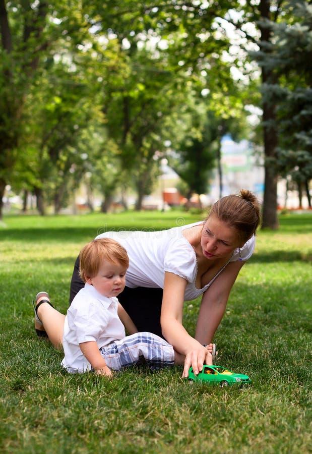 Juegos de la madre con el niño con el coche del juguete fotografía de archivo