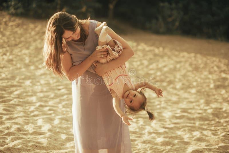 Juegos de la madre con su pequeña hija imagenes de archivo