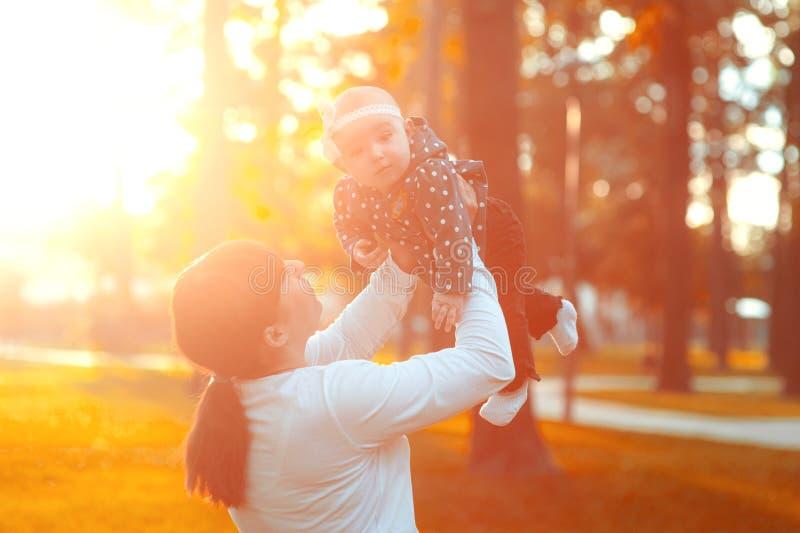Juegos de la mamá con su pequeña hija, mujer feliz y linda joven gozando y jugando con su hija del bebé que la detiene fotos de archivo
