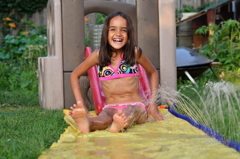 Juegos de la muchacha en su patio trasero fotografía de archivo libre de regalías
