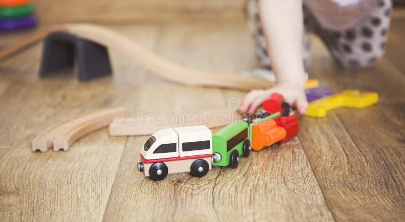 Juegos de la niña con los juguetes, el ferrocarril de madera y el tren fotografía de archivo