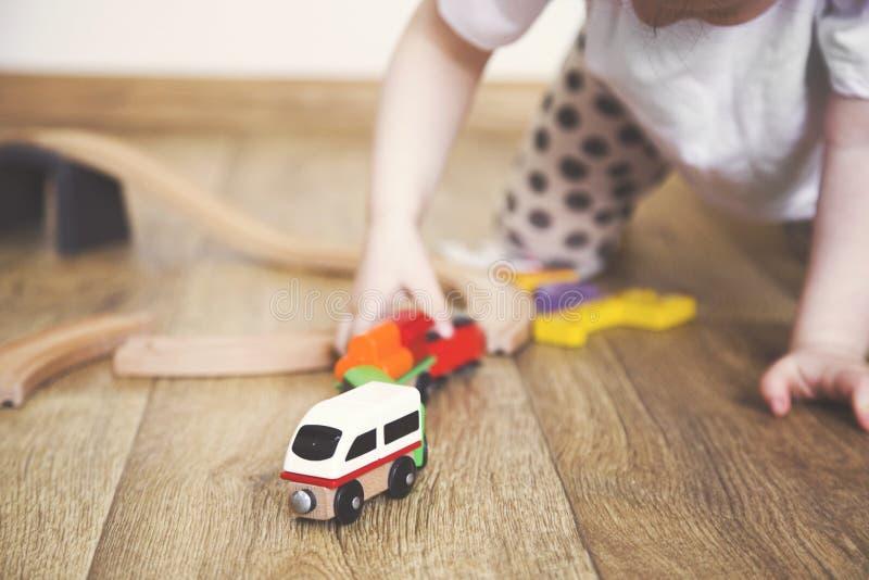 Juegos de la niña con los juguetes, el ferrocarril de madera y el tren fotos de archivo libres de regalías