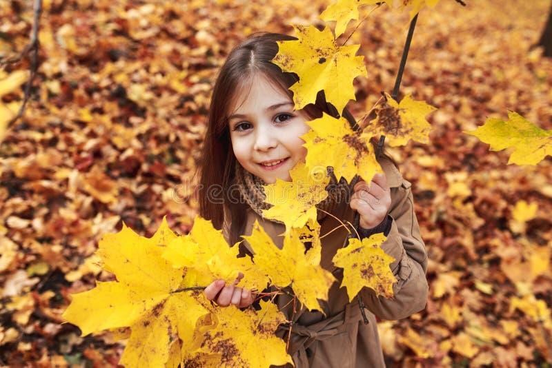 Juegos de la niña en Autumn Leaves en parque imágenes de archivo libres de regalías