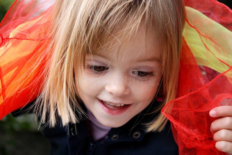 Juegos de la niña pequeña con las bufandas de seda fotos de archivo