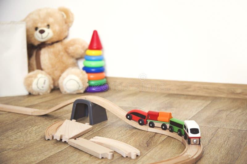 Juegos de la ni?a con los juguetes, el ferrocarril de madera y el tren fotografía de archivo libre de regalías