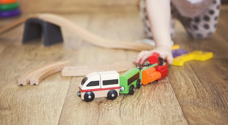 Juegos de la ni?a con los juguetes, el ferrocarril de madera y el tren foto de archivo libre de regalías